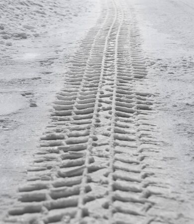 Tire track from heavy vehicle in snow on road photo