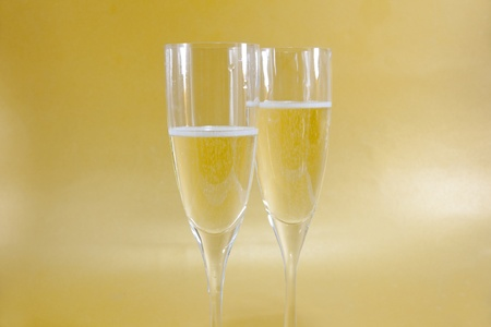Two champagne flutes with golden background photo