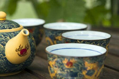 yellow tea pot: Chinese teapot and tea cups on a table in summer