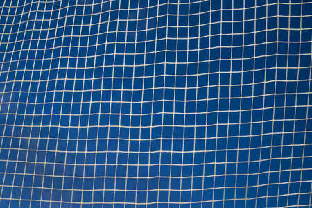 Closeup of white soccer net over blue sky  photo