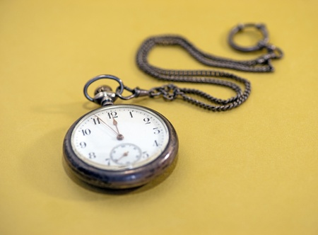 watch over: Close up of vintage pocket watch over golden background Stock Photo