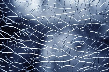 glass broken: Cerca de cristal destrozado sobre fondo azul
