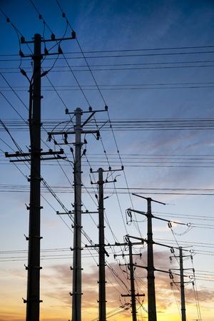 torres el�ctricas: Postes de electricidad en color cielo al atardecer Foto de archivo