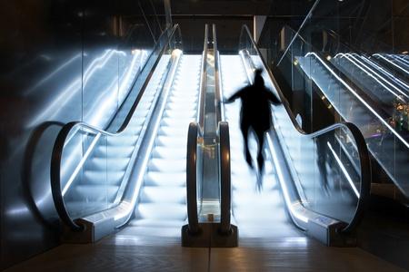 Una persona subiendo brillantemente iluminado escalera mec�nica Foto de archivo - 9195672