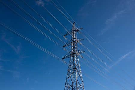 Electricity pylon on blue sky in bright sunshine photo