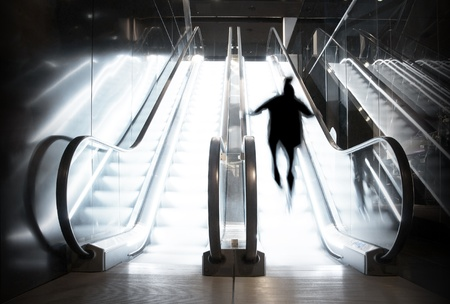A person going up brightly lit escalator