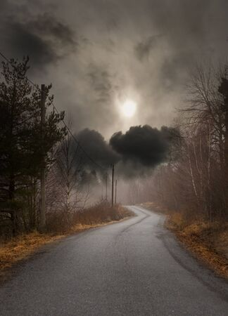 Narrow country road on gloomy autumn day Stock Photo
