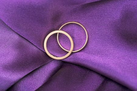 Two wedding rings on purple silk Stock Photo