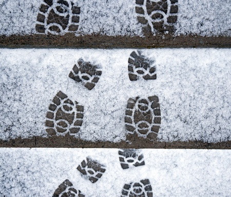 Shoe prints in snow on concrete staircase
