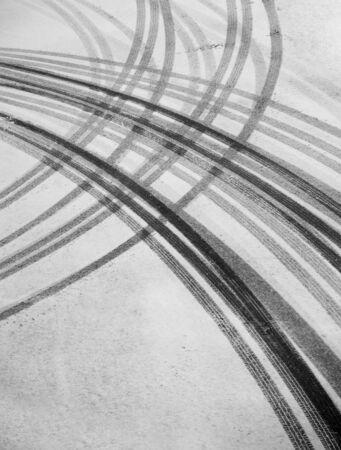 huellas de neumaticos: Huellas de neum�ticos sobre el asfalto en la nieve Foto de archivo