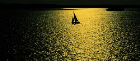 Sailing boat at sunset reflected in the water Stock Photo - 9735384