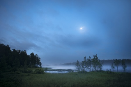 Fog over a lake in early morning in Hälsingland, Sweden Stock Photo