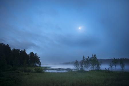 early fog: Fog over a lake in early morning in Hälsingland, Sweden
