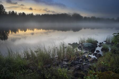 Fog over lake in Hälsingland, Sweden, in the early morning Stock Photo - 10080508