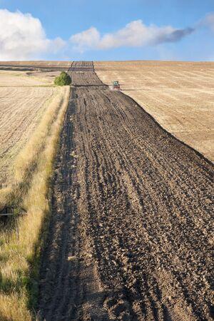arando: Tractor arando un campo grande