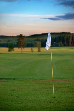 Flag on golf course in evening light photo