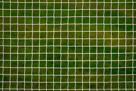 White sports net in front of green field Stock Photo
