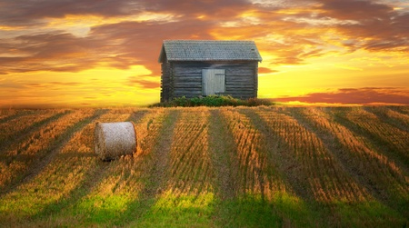 Rural landscape in evening with hay bale in focus in foreground and abandoned shed in background Stock Photo - 10562886