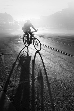 Silhouette of cyclist at sunrise, casting a long shadow photo