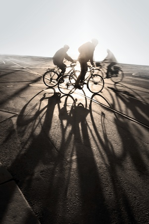 Silhouette of cyclists at sunrise, casting long shadows photo