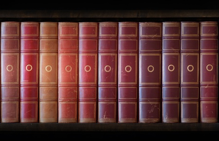 Vintage books in different shades of red and brown in bookcase photo
