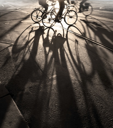 city bike: Silhouette of cyclists at sunrise Stock Photo