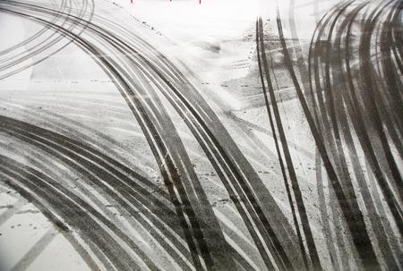 tire tracks on asphalt in snow