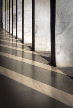 Columns with sunlight in the gaps and reflected in shiny floor photo