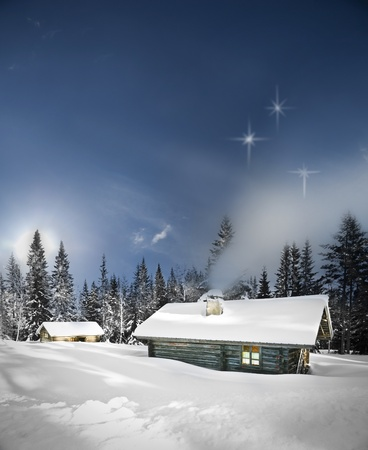 Remote log cabin in winter evening with stars in sky photo