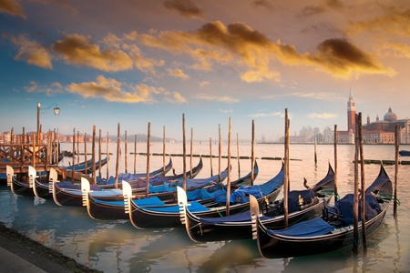 Moored gondolas in a row in evening light in Venice, Italy photo