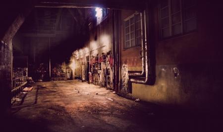 urban colors: Oscuro patio posterior de la vendimia con el graffiti Editorial