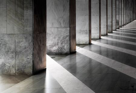 Row of columns with sunlight in the gaps and reflected in shiny floor  photo