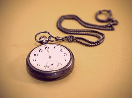 Close up of vintage pocket watch over golden background, fous on 12 oclock photo