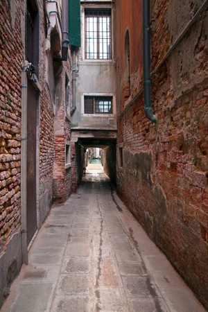 Narrow street in Venice, Italy, ending at a getty in a canal photo