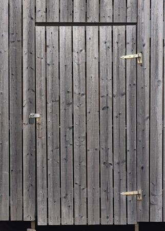 Grey door with hinges and padlock on wooden wall photo