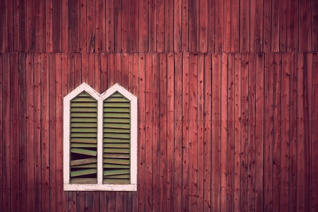 Red wooden rustic wall with window and broken shutters Stock Photo