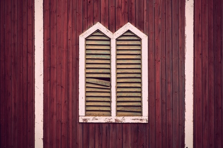 Window frame with shutters on rustic red wooden wall photo