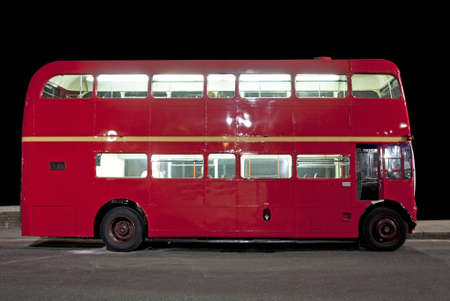 Traditional red double decker london bus at night photo