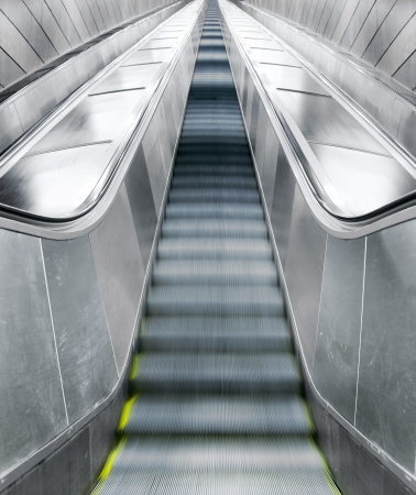 Empty long escalator in blurred motion and sparse composition photo