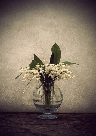Still life with lily-of-the-valley flowers in a vase with vintage look photo