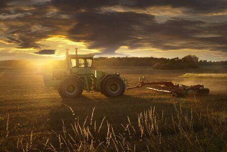 Tractor plowing a field at sunset in late summer photo