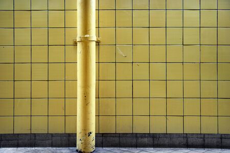 tatty: grunge tiled wall with painted metal pipe  Stock Photo