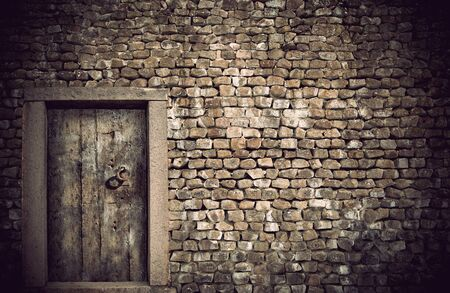 Ancient wooden door in wall built with natural rocks photo