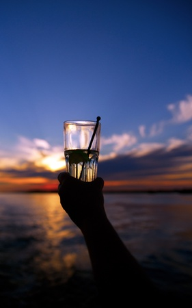 Hand holding glass with drink on beautiful sunset by the sea photo