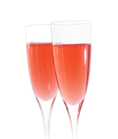 sparse: Two champagne flutes with pink champagne isolated on white