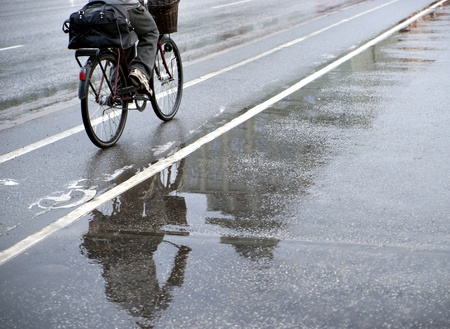 bicycle lane: Cyclist on bicycle path on rainy day. Focus on reflection in water. Stock Photo