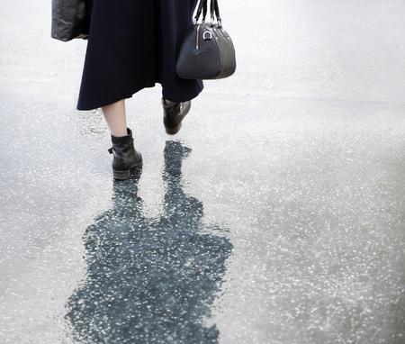 Ältere Dame mit Handtasche bei einem Spaziergang an einem regnerischen Tag