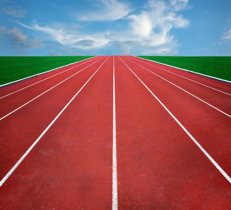 lane: Running track with blue cloudy sky in distance Stock Photo