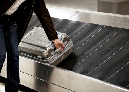 travel luggage: Man picking up metal suitcase from conveyor belt at airport