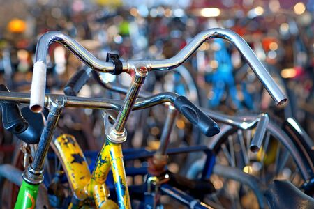 tatty: Close up of handles of old tatty yellow bike in big bicycle park